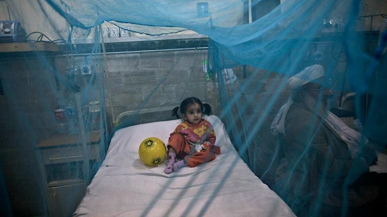 En ung flicka på en sjukhussäng täckt av blått myggnät.