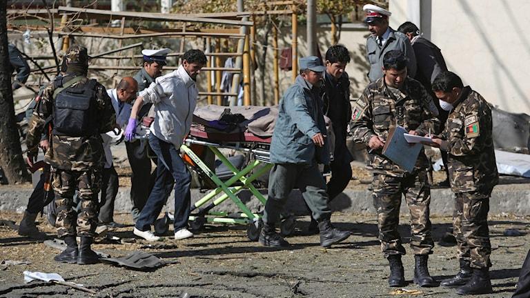 Skadad person får hjälp av ambulanspersonal efter självmordsattack i Kabul, Afghanistan. Foto: TT
