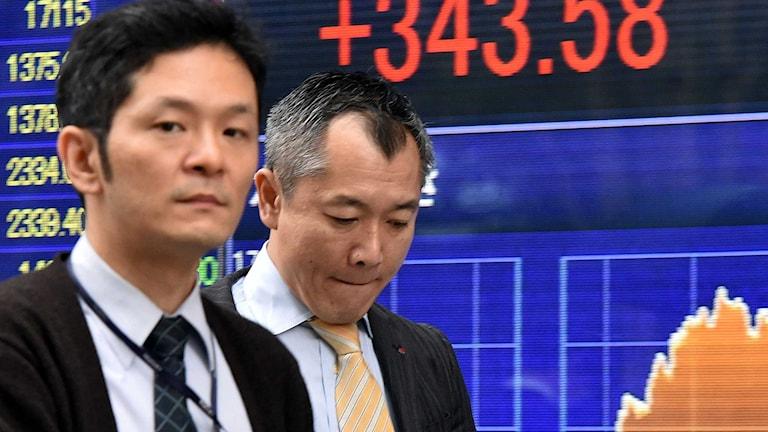 Japanska affärsmän passerar en börsskärm i Tokyo. Foto: Yoshikazu Tsuno/AFP/TT.