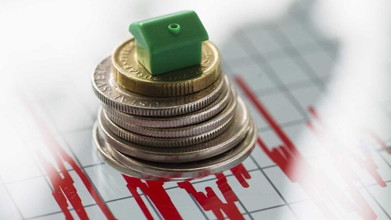 Ett litet hus på en stapel av mynt illustrerar kostnad för boende.