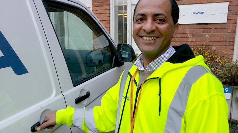 Habtewold Getahun ler framför sin tjänstebil hos Skanska.