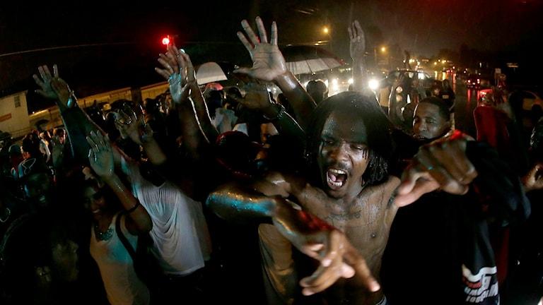 Arga demonstranter sträcker händerna mot kameran.
