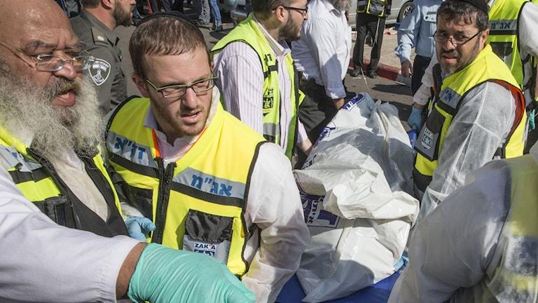Israeliska sjukvårdsvolontärer för bort en av de dödade palestiniernas kroppar. Foto: JACK GUEZ /TT