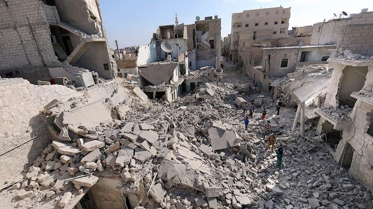 Aleppobor går runt i förödelsen efter oljefatsbomber. Foto: Zein al-Rifai/TT.