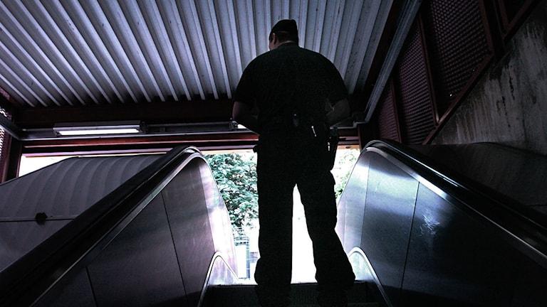 En polis i en rulltrappa i tunnelbanan.