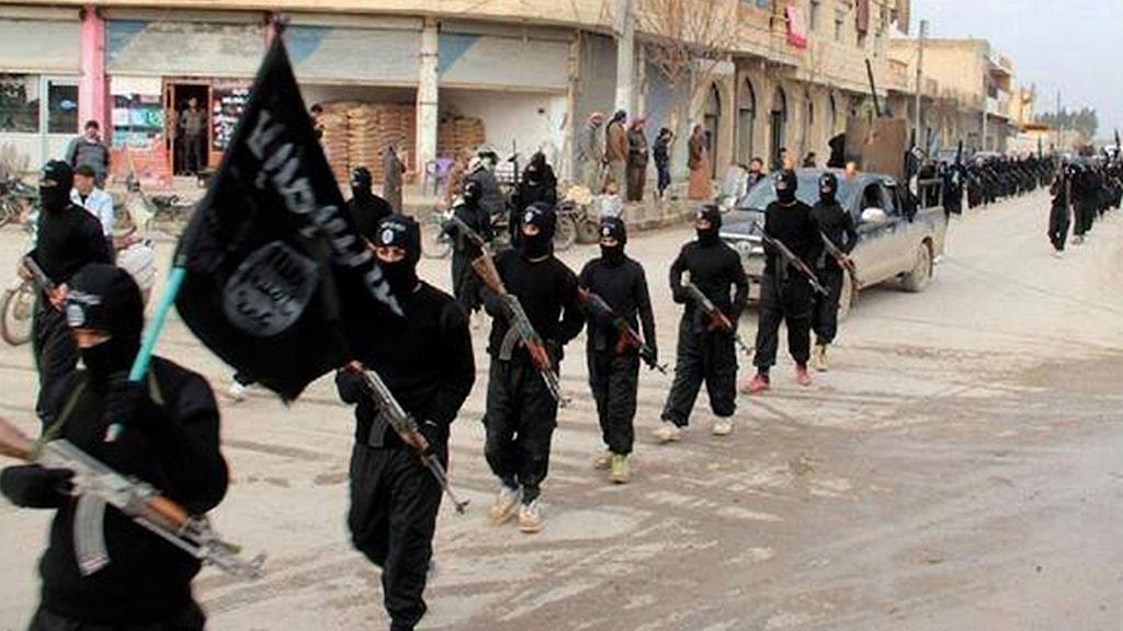 Soldater från Islamiska staten som tågar på en gata.