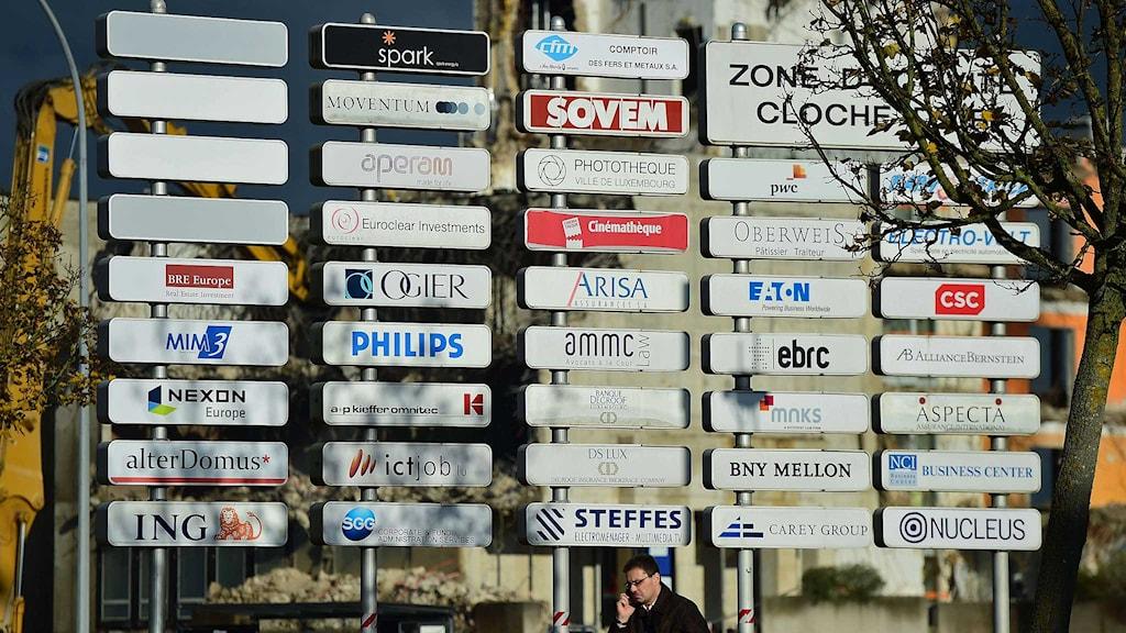 En man med mobiltelefon går förbi en stor tavla med olika företagsnamn i Luxemburg. Foto: Emmanuel Dunand/TT.