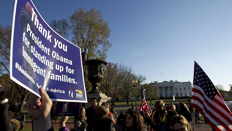 Människor står utanför Vita Huset i Washington, USA, och håller upp en skylt där de tackar president Obama. Foto: Jose Luis Magana/TT.