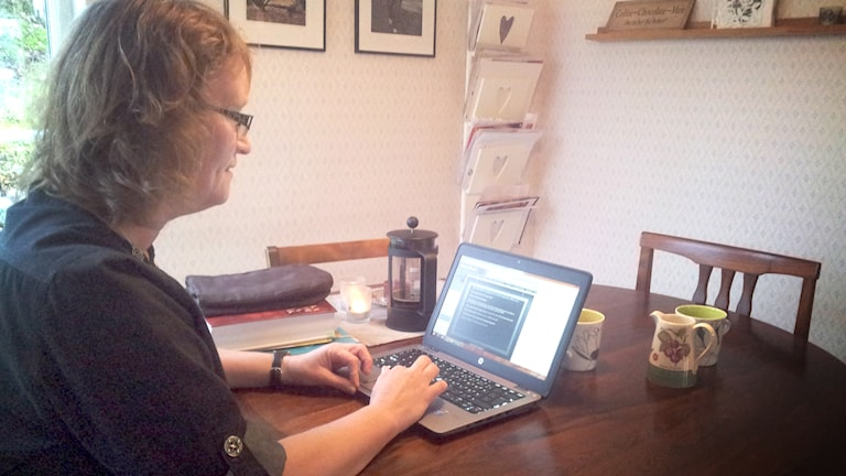 Malin Jonason, sitter vid köksbordet och försöker hitta rätt i skolans alla digitala rum. Foto: Carina Holmberg/Sveriges Radio