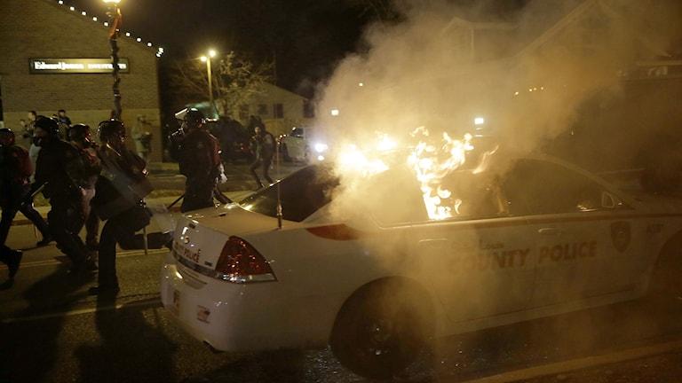 En polisbil vandaliseras i Ferguson efter beskedet att den polis som sköt den 18-årige Michael Brown till döds i augusti inte åtalas. Foto: David Goldman/TT.