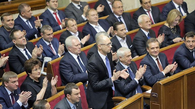 Ukrainas lagstiftare applåderar efter att premiärminister Arseniy Yatsenyuk utsågs till premiärministern under parlamentets öppnande. Foto: AP Photo / Efrem Lukatsky / TT.