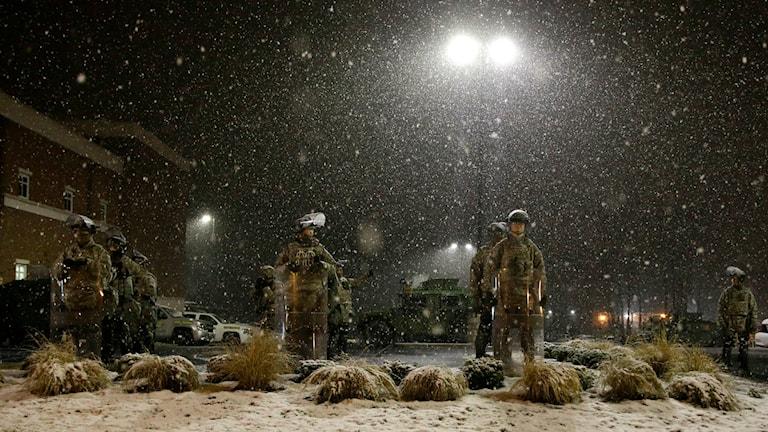 Snö faller över soldater med kravallsköldar stående under en lykta.