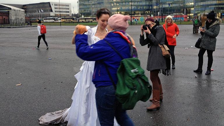 Ett lesbiskt brudpar dansar i regnet efter beskedet att Finlands riksdag säger ja till en könsneutral äktenskapslag. Foto: Thella Johnson / Sveriges Radio.
