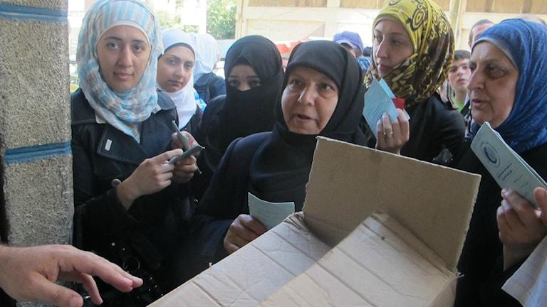 Syriska kvinnor i slöjor håller upp matkuponger för en man med en låda mat.