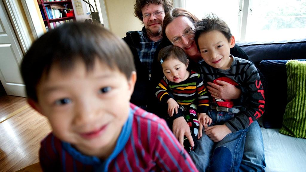 En leende pojke lutar sig mot kameran medan hans familj sitter i soffa i bakgrunden.