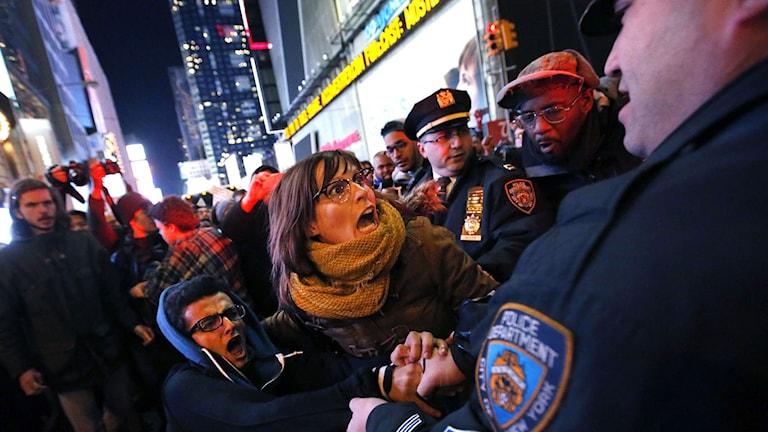 Protester på Times Square i New York efter åtalsjuryns beslut att låta en polis som tog stryptag på en man som dog under gripandet gå fri. Foto: TT/AP/Jason DeCrow