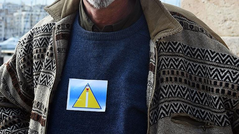 En man bär en triangel på bröstet i protest mot id-kort för hemlösa med samma symbol. Foto: Anne-Christine Poujoulat/TT.