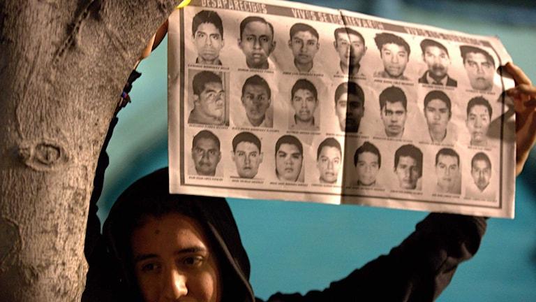 En demonstrant håller upp en affisch med foton på en del av de 43 försvunna lärarstudenterna. Foto: Eduardo Verdugo/TT.