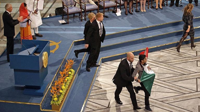 Aktivist förs bort från scenen när Nobels fredspris delas ut i Oslo. Foto: Matt Dunham/TT.