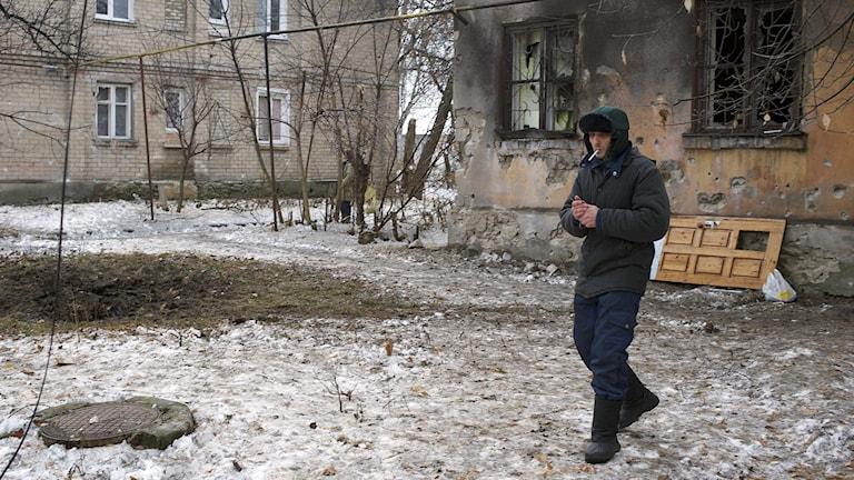 En man går förbi ett hus i östra Ukraina som förstörts i en granatattack. Foto: Balint Szlanko/TT.
