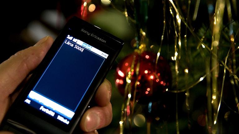 En person håller i en mobiltelefon för att göra ett sms-lån. Foto: Pontus Lundahl /TT.