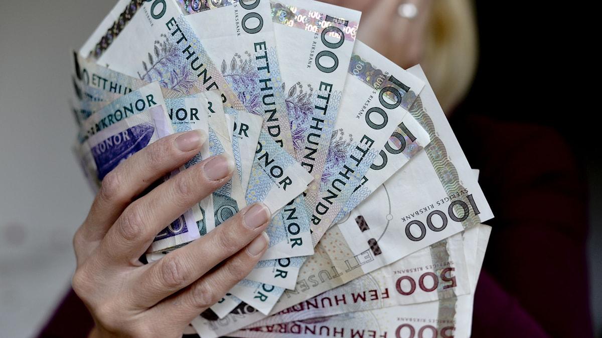 En kvinna med en bunt svenska sedlar i handen. Kvinnan i bilden har inget med artikeln att göra. Foto: Pontus Lundahl/ TT.
