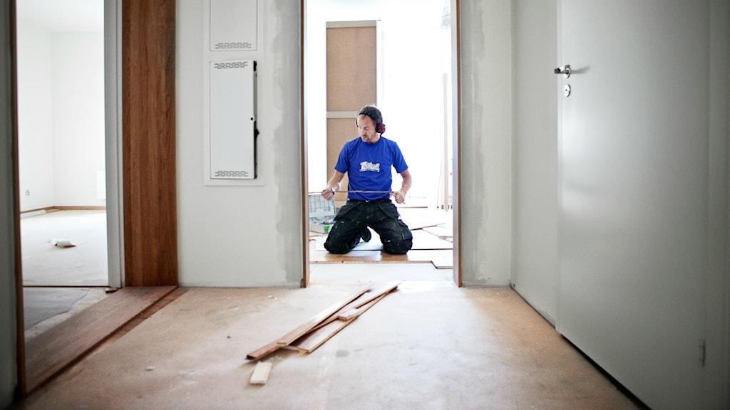 Hantverkare på knä i en dörröppning