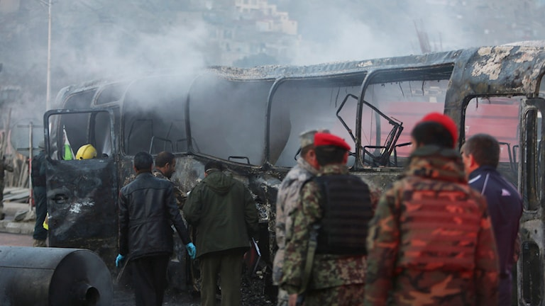Soldater intill en buss som sprängts i Afghanistan. Foto: Rahmat Gul/AP.