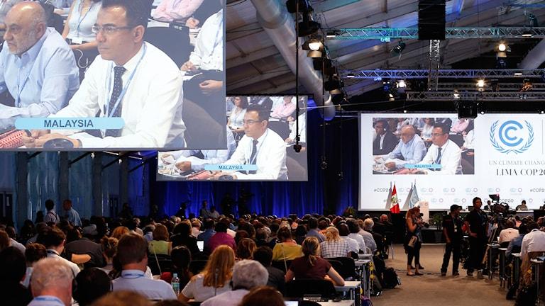 Många människor sitter framför en scen, på stora bildskärmar visas en representant från Malaysia. Det ser man på skylten framför honom på skrivbordet.