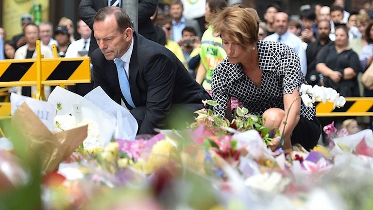 Australiens premiärminister Tony Abbott och hans hustru Margareta lägger blommor vid ett minnesmärke nära platsen där det tragiska gisslandramat utspelade sig i går. Foto: Peter Parks/ Afp/ TT.