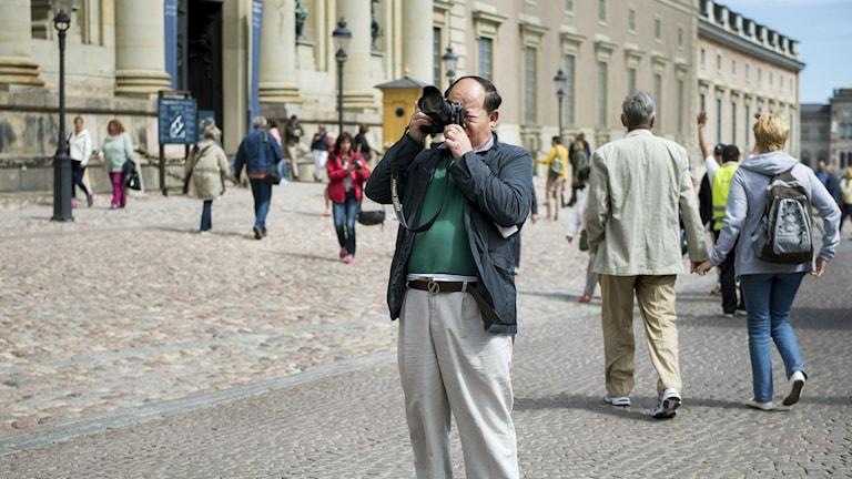 Turist fotograferar utanför slottet i Stockholm. Foto: Ari Luostarinen / TT