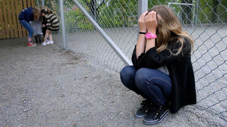 En flicka sitter med händerna för ansiktet. Foto: Janerik Henriksson/TT.