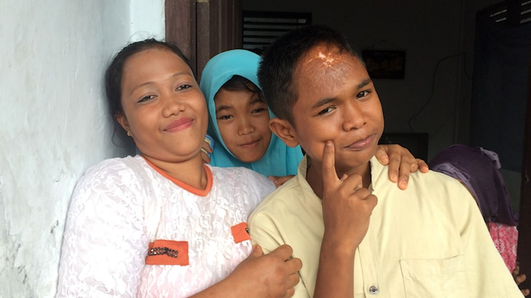 Roudha, i mitten, och Arif, till höger upplevde de där många timmarna på havet tillsammans, något de inte minns idag. Här busandes med en släkting.