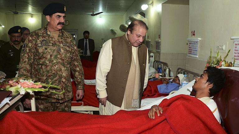 Nawaz Sharif besöker en av ungdomarna som överlevde skolmassakern i tisdags. Foto: AFP/TT.