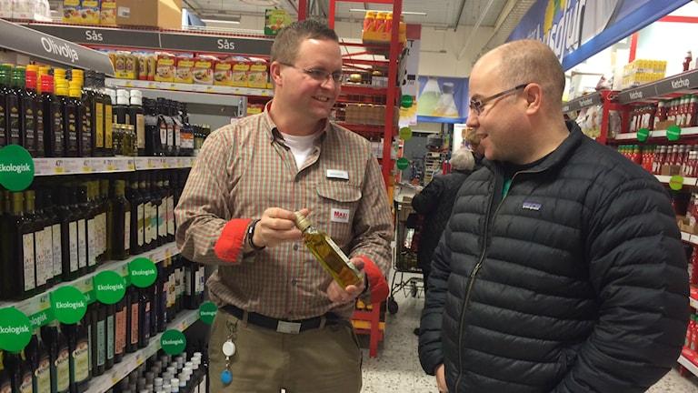Magnus Winges (tv) butikschef i Gävle och Sven-Olov Daunfeldt, forskningschef HUI Research vid hyllan med olivoljor, en produkt där försäljningen av ekologiskt ökat med 48 procent med den nya tydligare skyltningen. Foto: Jenny Roosqvist / Sveriges Radio.