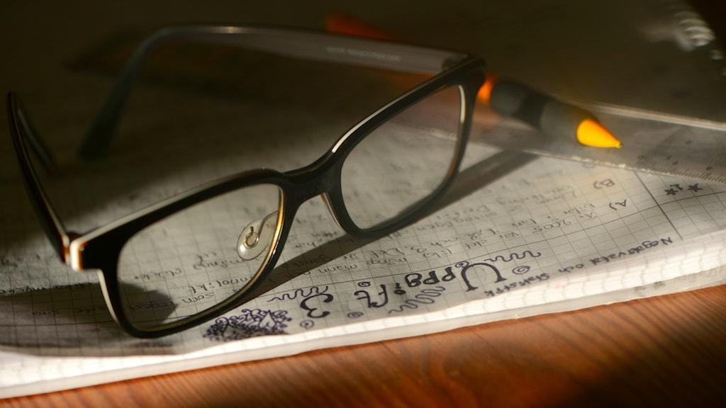 Ett par glasögon och en penna på ett anteckningsblock.