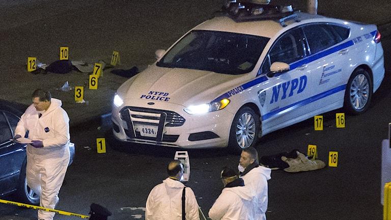Polis undersöker bilen som de dödade satt i. Foto: John Minchillo/TT.
