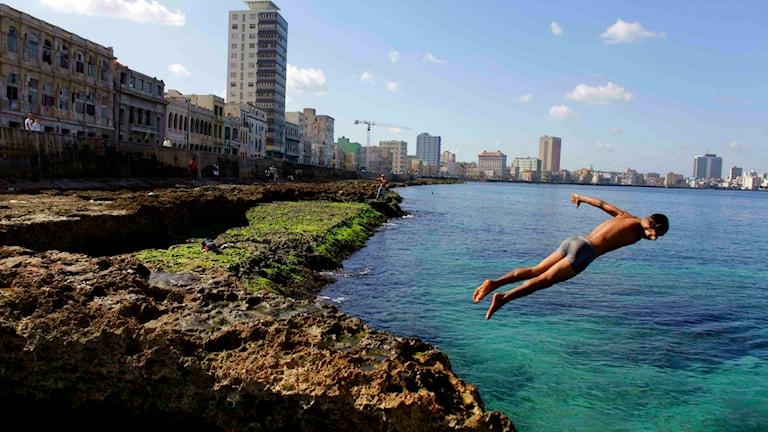 En pojke dyker i vattnet i Havanna
