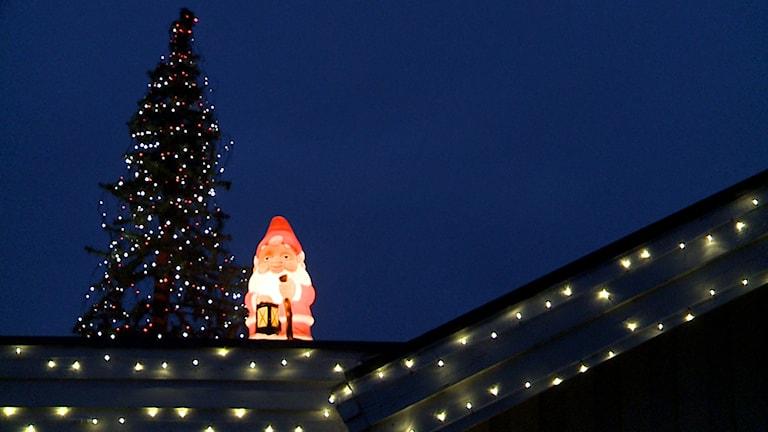 Jultomte, gran och ljusslingor som dekoration på ett hustak. Foto: Erland Vinberg/TT.