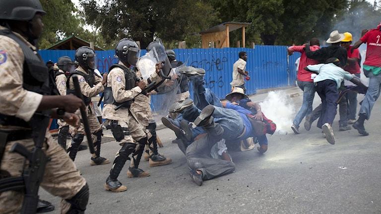 Polis och demonstranter drabbar samman vid protester mot regeringen i Haiti. Foto:Dieu Nalio Chery/TT.