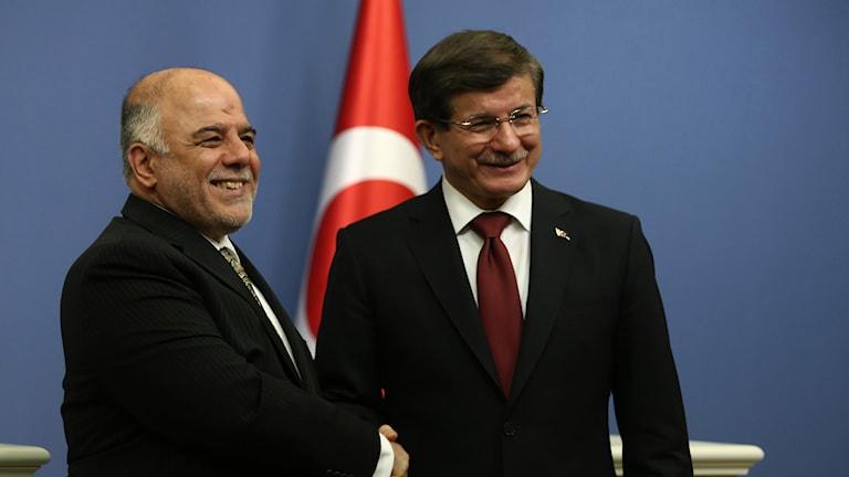 Den turkiske premiärministern Ahmet Davutoglu skakar hand med sin irakiske kollega Haider al-Abadi. Foto: TT.