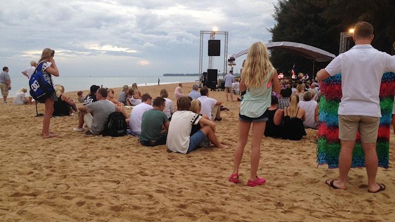 Anhöriga och vänner till de som omkom sitter på stranden i Khao Lak och tar del av minnestunden. Foto: Karin Wickström/Sveriges Radio.