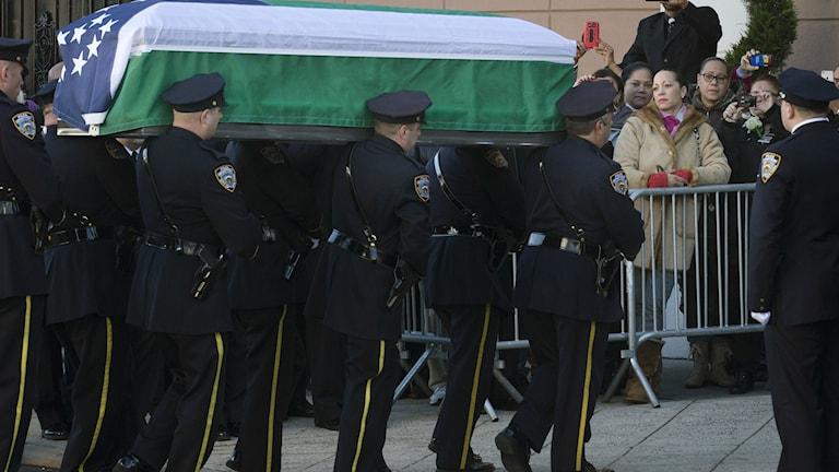 Kista med mördad New York-polis förs till Queens. Foto: John Minchillo/TT.