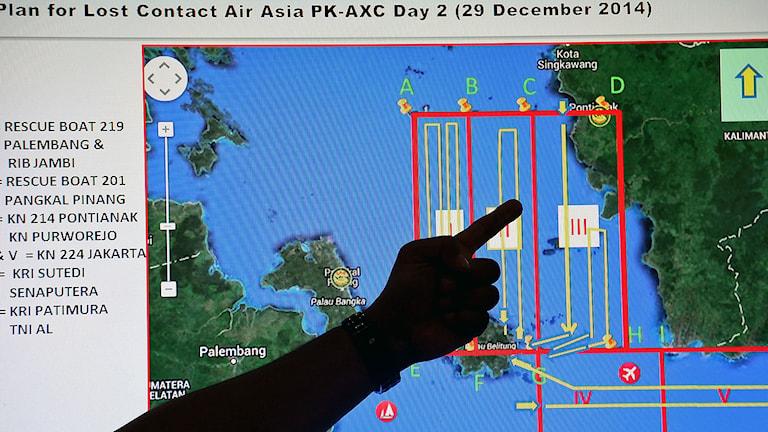 Personal i indonesiska nationella sjöräddningsmyndigheten (BASARNAS) pekar på en karta över ett sökområde inför en räddningsoperation av de saknade Air Asia-flygplanet QZ8501. Foto: AP Photo / Tatan Syuflana / TT.