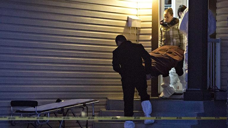 Poliser bär ut en kropp i en liksäck från ett hus i Edmonton i Kanada. Foto: Jason Franson/TT.