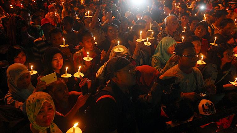 Indoneser tänder ljus för offren i flygolyckan i Javasjön. Foto: TT.