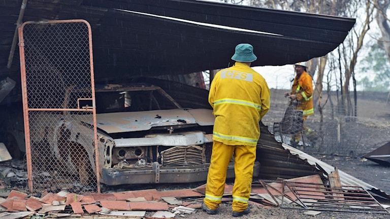 Brandmän intill ett utbränt skjul i Adelaide Hills. Foto: Brenton Edwards/AFP.