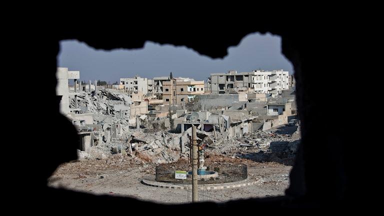 Bild tagen från ett sönderbombat hus i staden Kobani i norra Syrien. Fler sönderbombade hus syns i bakgrunden. Foto: Jake Simkin/TT.
