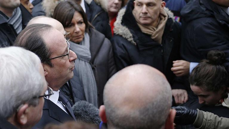 Frankrikes president Francois Hollande pratar med pressen bredvid Paris borgmästare Anne Hidalgo efter hans ankomst till huvudkontoret för den franska satirtidningen Charlie Hebdo i Paris. Foto: AFP PHOTO/ KENZO TRIBOUILLARD/ TT.