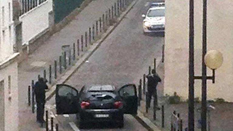 Poliser möter maskerade beväpnade män nära kontoret för den franska satirtidningen Charlie Hebdo i Paris. Foto: AFP PHOTO/ ANNE GELBARD/TT.